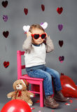 Little baby boy toddler sitting on small pink chair with bear toy in studio wearing red funny glasses Royalty Free Stock Photos