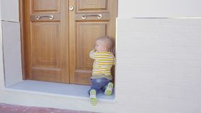 Little baby boy try to open wood gate of a house. Hd stock video footage