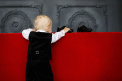 Little baby boy trying to wear patent leather shoes Royalty Free Stock Image