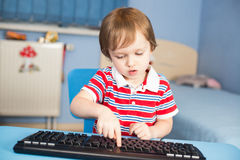 Little baby boy typing on computer keyboard Stock Photo