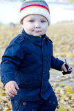 Little baby boy walking away in colorful autumn park Stock Image