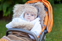 Little baby boy in warm winter clothes outdoor. Little baby boy in warm winter clothes and orange pram outdoor Stock Photo