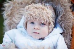 Little baby boy in warm winter clothes outdoor. Little baby boy in warm winter clothes and orange pram outdoor Stock Photo