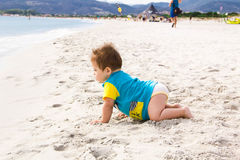Little baby boy wearing blue rash guard suit playing on tropical ocean beach. UV and sun protection for young children. Toddler ki Royalty Free Stock Image