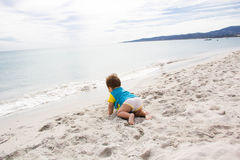 Little baby boy wearing blue rash guard suit playing on tropical ocean beach. UV and sun protection for young children. Toddler ki Royalty Free Stock Images