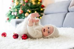 Little baby boy in white knitted onesie, playing with and opening presents at home