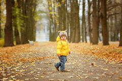 Little baby boy in yellow jacket smiles in autumn Royalty Free Stock Images