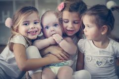 Little baby brother poses to camera with little sisters. royalty free stock photos