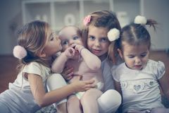Little baby brother poses to camera with little sisters. stock photography