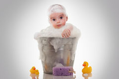 Little baby on a bucket on white background Stock Photos