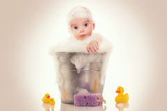 Little baby on a bucket on white Royalty Free Stock Photography