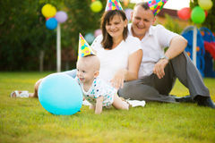 Little baby in cap on his birthday. With parent on background Royalty Free Stock Photography