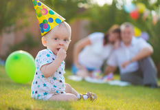 Little baby in cap on his birthday. With parent on background Stock Image