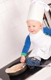 Little baby chef in the cook hat making pancakes Royalty Free Stock Photo