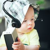 Infant Baby Child Boy Six Months Old with Sound Speaker and Headphones. Little Baby Child Boy Six Months Old with Sound Speaker and Headphones royalty free stock image