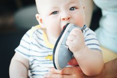 Infant Baby Child Boy Six Months Old is Takes his Shoe in the Mouth. Little Baby Child Boy Six Months Old is Takes his Shoe in the Mouth royalty free stock photography