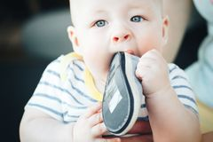 Infant Baby Child Boy Six Months Old is Takes his Shoe in the Mouth. Little Baby Child Boy Six Months Old is Takes his Shoe in the Mouth stock photos