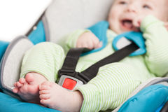 Little baby child in safety car seat. Little smiling baby child fastened with security belt in safety car seat Royalty Free Stock Images