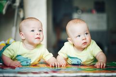 Infant Baby Child Twins Brothers Six Months Old is Playing on the Floor. Little Baby Child Twins Brothers Six Months Old is Playing on the Floor royalty free stock images