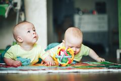 Infant Baby Child Twins Brothers Six Months Old is Playing on the Floor. Little Baby Child Twins Brothers Six Months Old is Playing on the Floor stock image