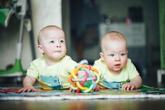 Infant Baby Child Twins Brothers Six Months Old is Playing on the Floor. Little Baby Child Twins Brothers Six Months Old is Playing on the Floor royalty free stock photo
