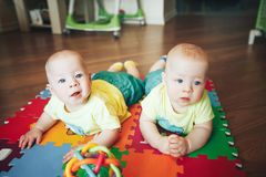 Infant Baby Child Twins Brothers Six Months Old is Playing on the Floor. Little Baby Child Twins Brothers Six Months Old is Playing on the Floor royalty free stock photography