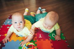 Infant Baby Child Twins Brothers Six Months Old is Playing on the Floor. Little Baby Child Twins Brothers Six Months Old is Playing on the Floor Royalty Free Stock Photos