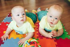 Infant Baby Child Twins Brothers Six Months Old is Playing on the Floor. Little Baby Child Twins Brothers Six Months Old is Playing on the Floor stock photos