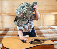 Little baby in cowboy hat playing acoustic guitar Stock Photo
