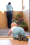 Little baby crawling to his father. Staying on terrace stock images