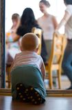 Little baby crawling to parents. Little baby crawling through door aperture to parents on terrace Royalty Free Stock Image