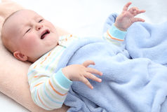 Little baby crying. In bed Royalty Free Stock Photography