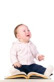 Little baby is crying with a book Royalty Free Stock Photos