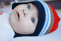 Little baby with cute hat, blue eyes and a tear in the corner of the blue eye Royalty Free Stock Photography
