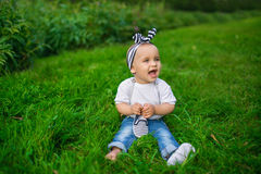 A little baby in a denim clothes sits on a grass Stock Image