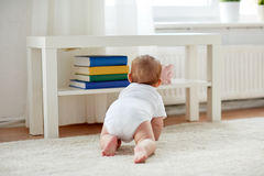 Little baby in diaper crawling on floor at home Stock Photo