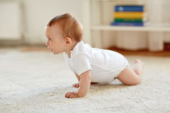 Little baby in diaper crawling on floor at home Stock Photos