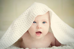 Little baby with Down syndrome hid under blanket Royalty Free Stock Photo