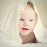 Little baby with Down syndrome hid under blanket Royalty Free Stock Photos