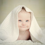 Little baby with Down syndrome hid under blanket and smiles slyly. Little baby with Down syndrome hid  under blanket and smiles slyly Royalty Free Stock Photos