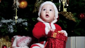 Little baby dressed in a Santa costume playing with Christmas gifts, cute boy sitting near Christmas tree, child stock video
