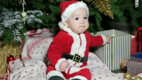 Little baby dressed in Santa outfits, cute boy playing near the Christmas tree, child in carnival costume plays at home stock footage