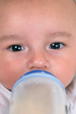 Little baby drinking milk from bottle Stock Image