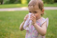 Little baby is drinking water from glass at sunny hot day royalty free stock photography