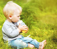 Little baby drinks from a bottle. Outdoors Stock Image