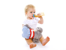 Little baby drinks from a bottle. On a white background Stock Photos