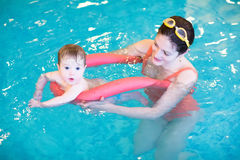 Little baby in an early swimming class. Adorable little baby in an early swimming class stock photos