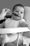 Little baby eating. Little baby girl eating in she's chair Royalty Free Stock Image