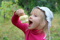 Little baby eating apple holding it in hand royalty free stock photos