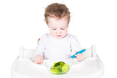 Little baby eating broccoli Stock Photos
